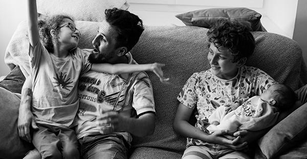 Une famille de quatre assise sur son canapé