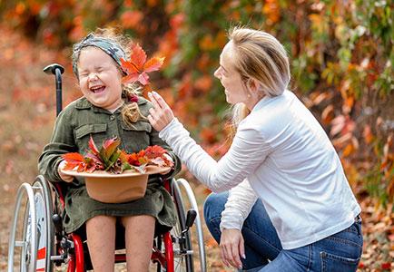 Mutter mit Kind im Rollstuhl, beide lachen